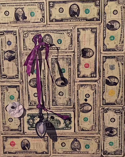 A spoon hangs from a ribbon against a page of paper money.